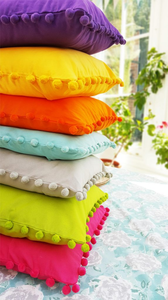 a pile of cotton pompom cushions in bright colours