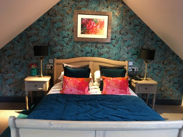 petrol blue bedcover and chrysanthemum cushions